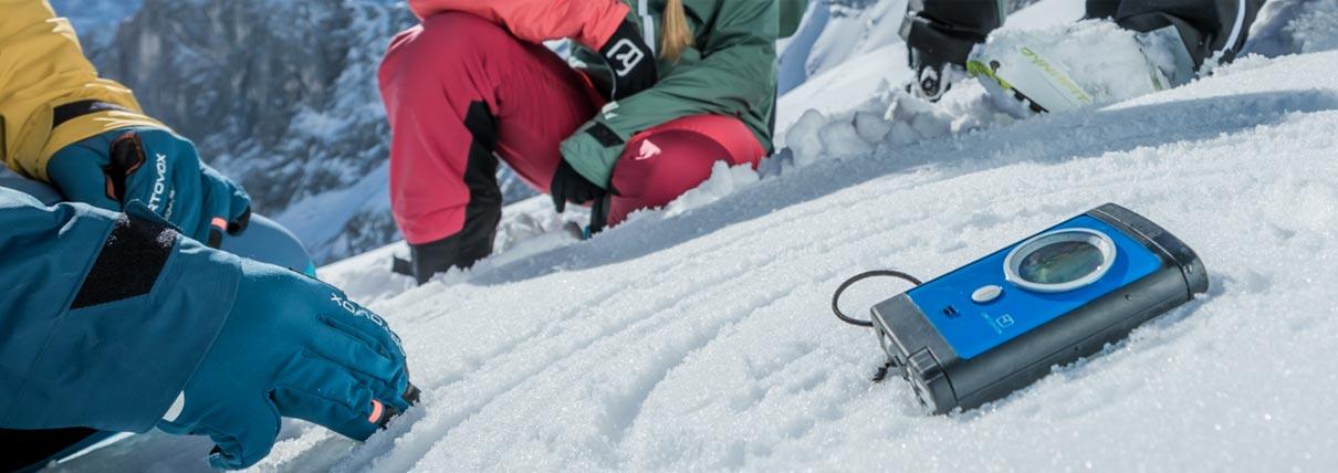 Persone che utilizzano un kit ARVA sulla neve fresca