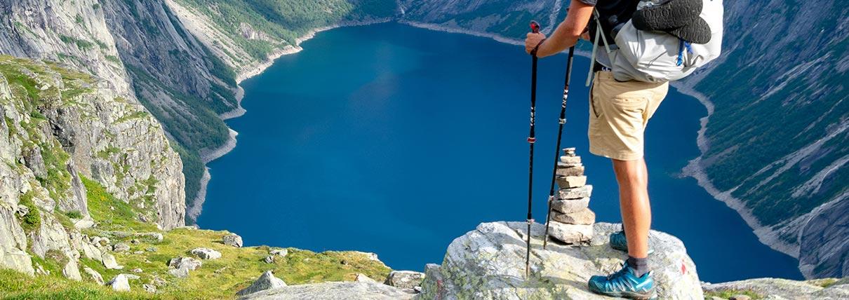 Persona che ammira un lago di montagna mentre passeggia con dei bastoncini Leki