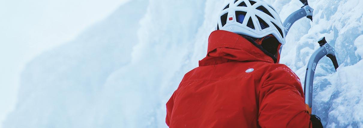 Uomo che scala una parete di ghiaccio con due piccozze
