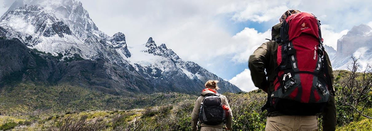 Una coppia che passeggia in montagna con lo zaino in spalla