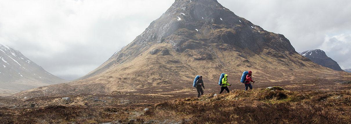 Tre persone con alle spalle degli zaini azzurri che passeggiano su un prato attorno alla vetta di una montagna