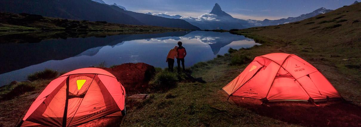 Una coppia che ammira un lago fra le montagne alla sera con alle spalle due tende rosse