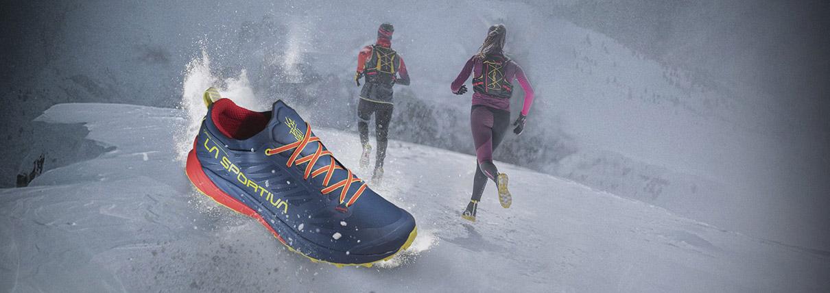 Scarpa La Sportiva di colore blu e gialla con sfondo due persone che corrono sulla neve
