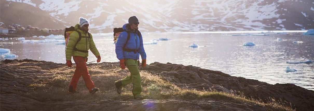 Due persone che passeggiano lungo la spiaggia di un lago di montagna