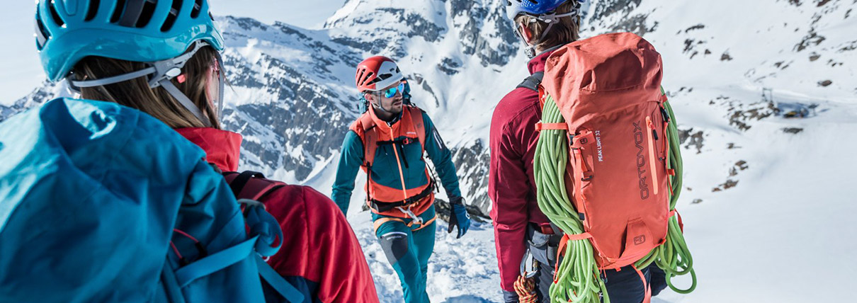 Tre persone con zaini e corde su una montagna innevata