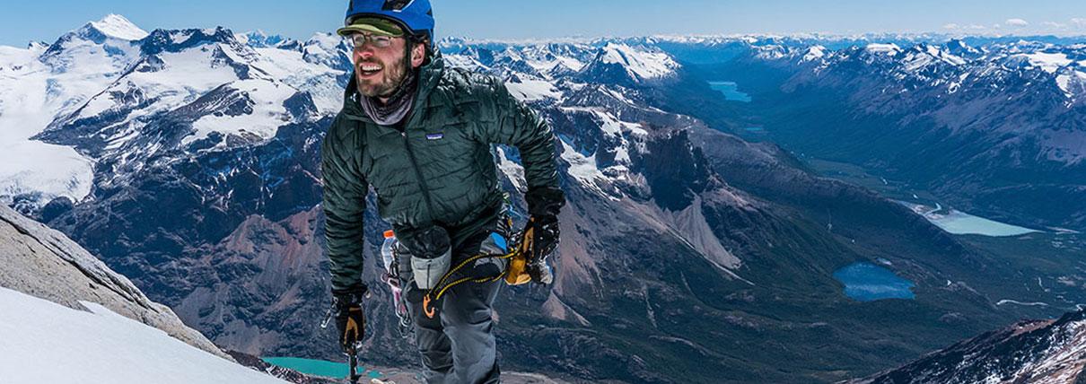 Persona che sta scalando la montagna con una piccozza