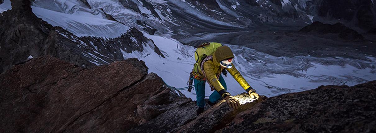 Persona che sta camminando lungo la cresta di una montagna con una torcia durante la sera